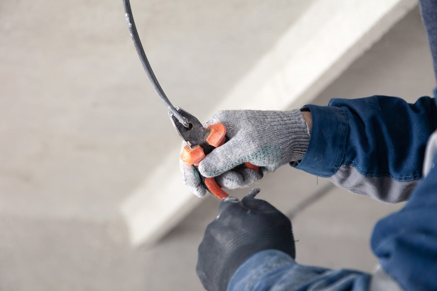 Electrician using pliers to repair an old wire