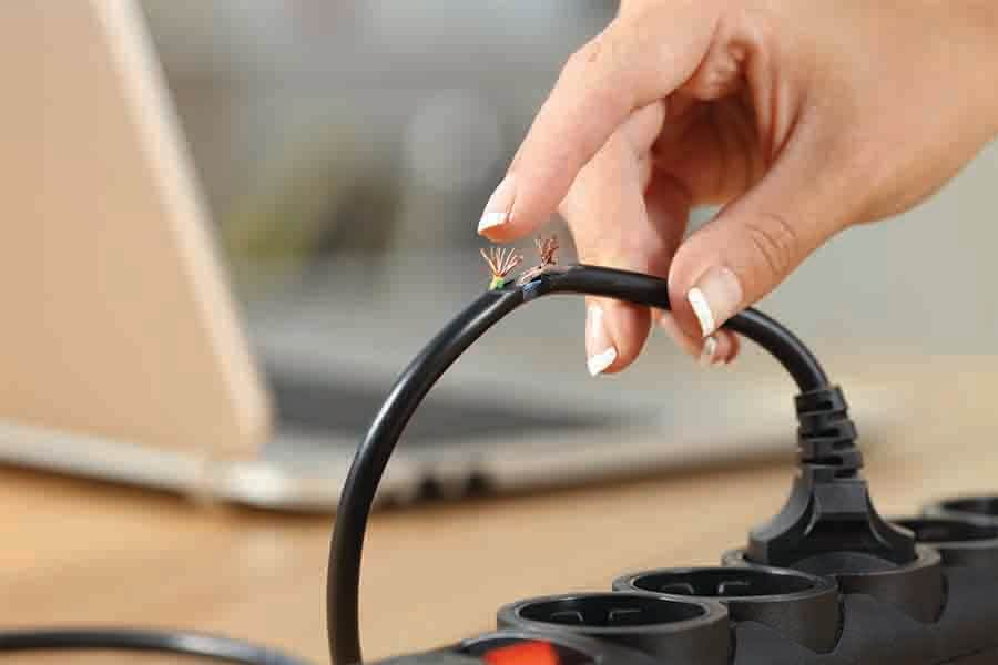 Women's hand holding a dangerous and damaged electrical cord